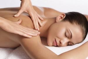 Woman having Swedish body massage treatment by beauty therapist